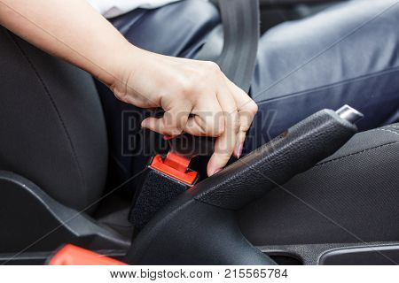 Young woman fastening seat belt in the car. Female driver driving secure