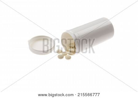 pills spilled from pills bottle. Pills and medicine container lying on white background.