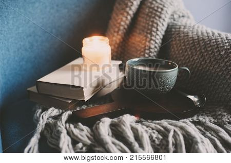 Cozy winter weekend at home. Morning with coffee or cocoa books warm knitted blanket and nordic style chair. Hygge concept.