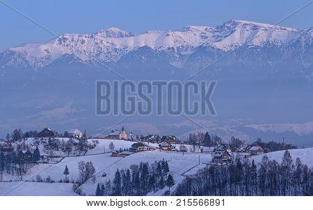 Evening fall over snowy Pestera village in the frozen valleys of Bucegi mountains Rucar-Bran pass Transylvania region Romania.