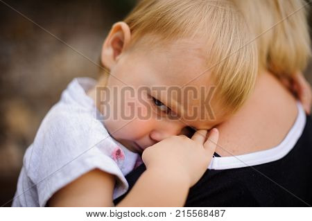 Cute blonde child dressed in a white shirt with serious look lying on mom's shoulder
