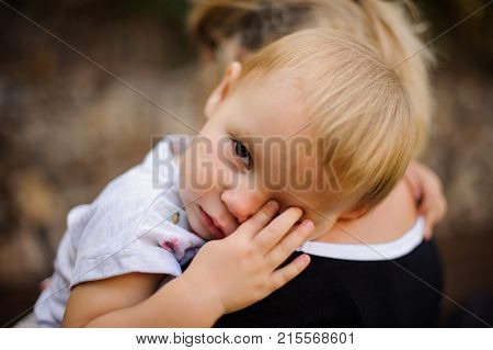 Little blonde child dressed in a white shirt lying on mom's shoulder and wiping eyes