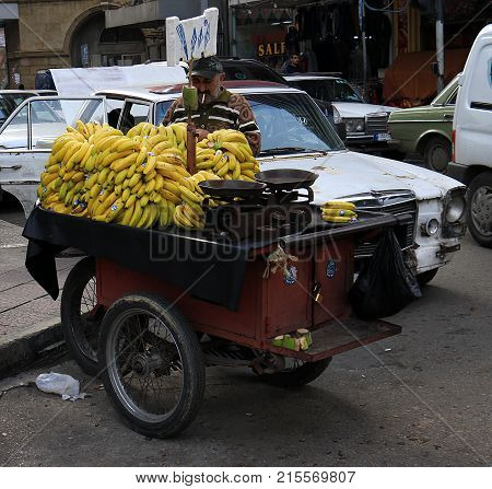TRIPOLI, LEBANON - 25 NOVEMBER 2017: An old man selling bananas on a cart with the price written on a board in the souk of Tripoli, Lebanon.