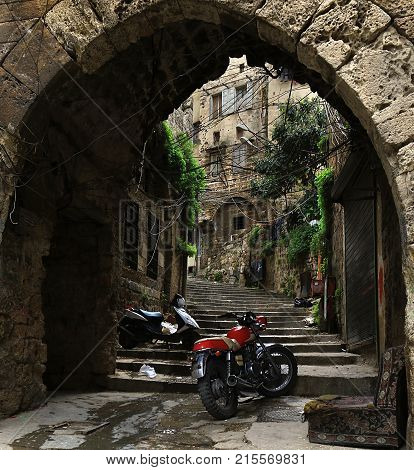 A discarded sofa with two motorcycles parked in an old alleyway in Tripoli Lebanon.