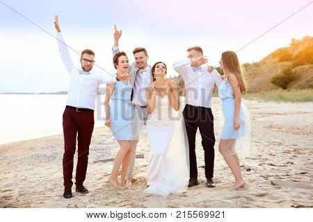 Happy wedding couple having fun with friends on beach