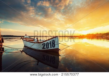 Happy New Year 2018 concept lettering on the Boat with a reflection in the water at sunset