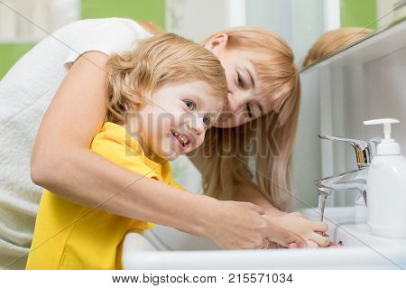 Mother and child son washing their hands in the bathroom. Care and concern for kids conception.