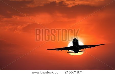 Silhouette of aircraft and orange sky with sun. Landscape with passenger airplane is flying in the sky with clouds at sunset. Travel background. Passenger airliner. Commercial airplane. Business