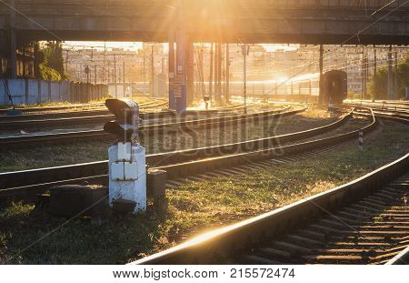 Beautiful scene with traffic light railroad and moving train at sunset. Railway station. Colorful industrial landscape with railway platform train and yellow sunlight. Railway transportation