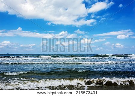 Seascape. Tidal wave blue sky with clouds and an endless horizon