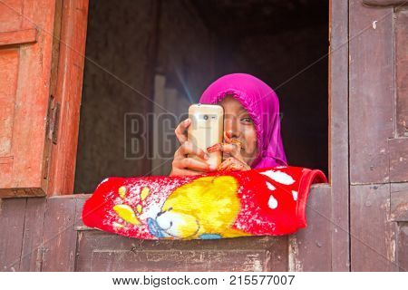 LOMBOK, INDONESIA - DECEMBER 30, 2016: muslim girl doing some mischief with her mobile phone in Lombok, Indonesia on the 30th of december 2016