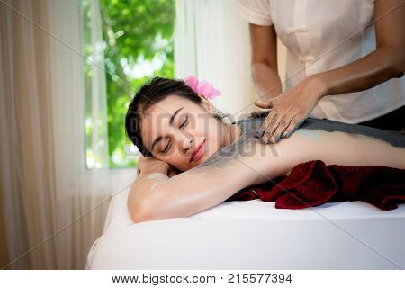 Masseur doing massage spa with treatment mud on Asian woman body in the Thai spa lifestyle so relax and luxury. Healthy Concept