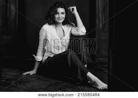 Monochrome Portraite of young, beautiful smiling woman actress with short brown hair in the studio