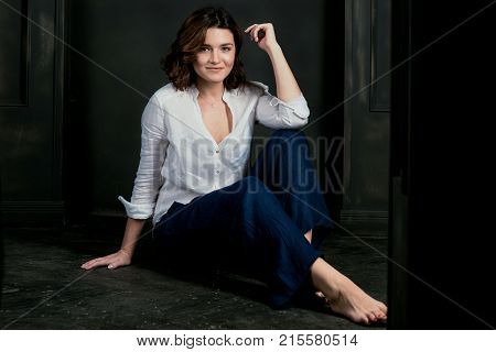 Portraite of young, beautiful smiling woman actress with short brown hair in the studio