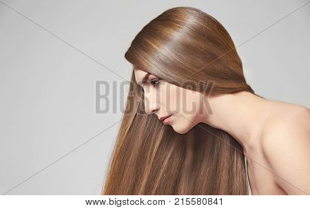 Young woman with beautiful long hair of caramel color on light background
