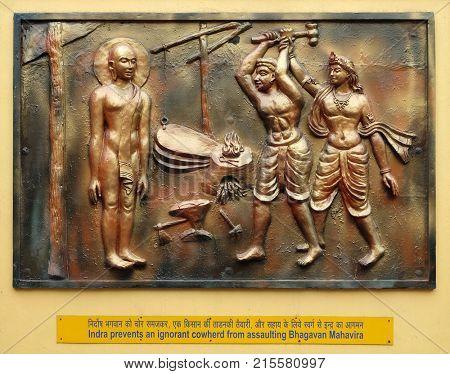 KOLKATA,INDIA - FEBRUARY 09: Indra prevents an ignorant cowherd from assaulting Bhagavan Mahavira, Street bass relief on the wall of Jain Temple in Kolkata, West Bengal, on February 09, 2016.