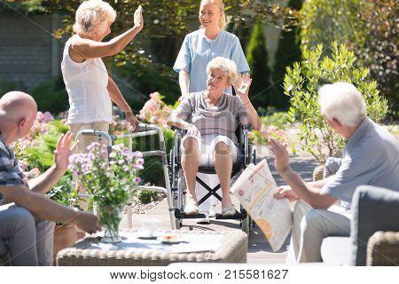 Senior People Welcoming Friend