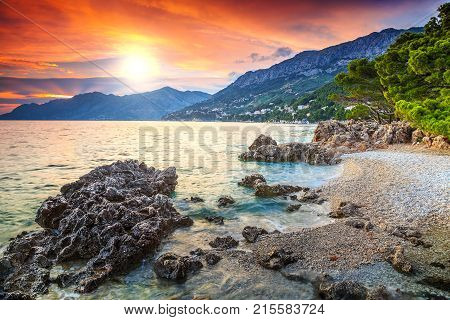 Beautiful gravel beach with Biokovo mountains on background and stunning colorful sunset, Brela, Makarska riviera, Dalmatia, Croatia, Europe