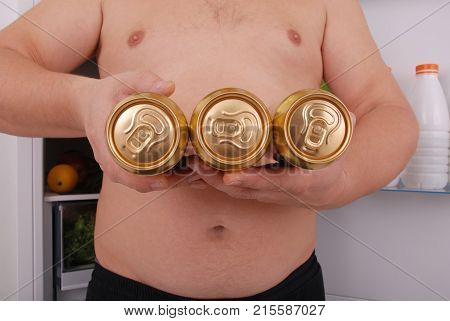 Man hold three can of beer on the refrigerator background. Man near the fridge.