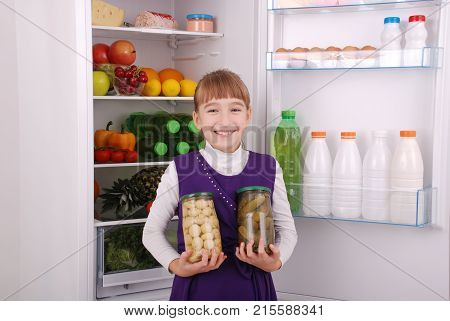 Young beautiful girl hold canned champignons and cucumbers on the refrigerator background. Fruits and vegetables in the refrigerator.