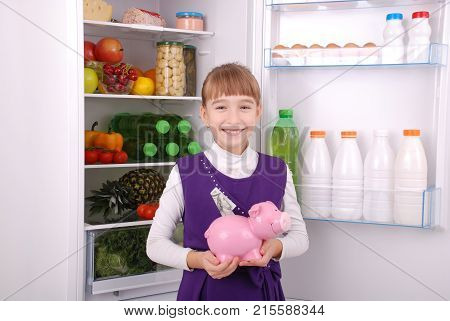 Young beautiful girl standing with piggy bank (money box) on the refrigerator background. Fruits and vegetables in the refrigerator.