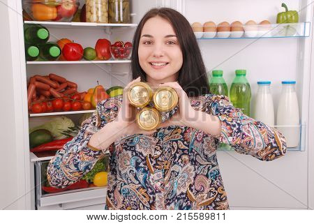 Young girl hold three can of beer on the refrigerator background. Beautiful young girl near the fridge.