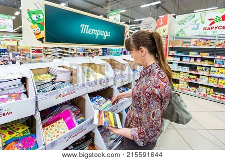 Samara Russia - September 3 2017: Woman choosing office supplies at shopping in superstore Karusel. Text in Russian: Writing-books