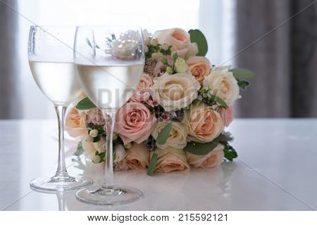 Beautiful bridal flowers bouquet on white reflecting table beside two glasses of white wine