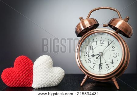 retro clock with love heart yarn on black background - love with time together concept.