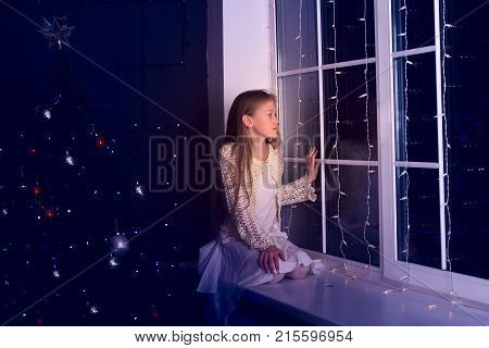 Dreaming Girl Teenager Sits On A Window Sill