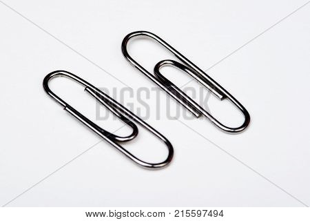 A lot of metal paperclips on a white background