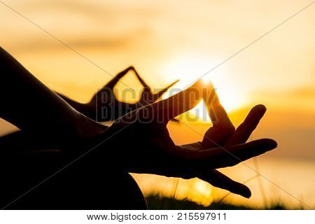 Close up hands. Woman do yoga outdoor. Woman exercising vital and meditation for fitness lifestyle in the beach sunset background. Healthy Concept