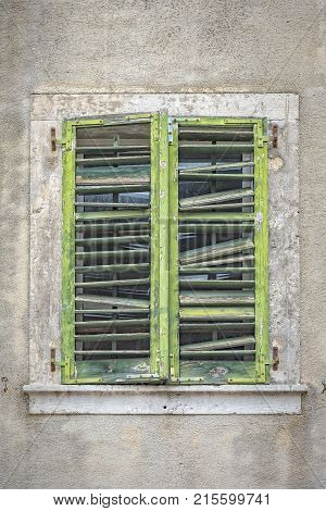 Old green shutters in need of repair cover a window in Kotor's old town in Montenegro.