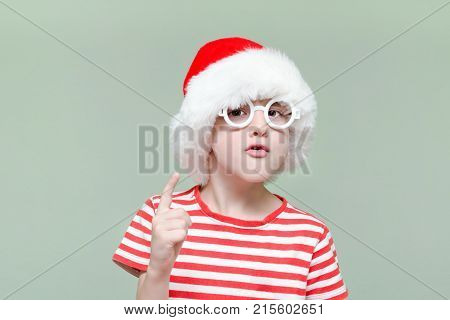 Disgruntled Boy In Santa's Hat And Glasses Threatens With A Finger