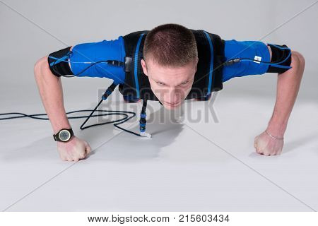 Man In An Electric Muscular Suit For Stimulation Does Push-ups On The Fists