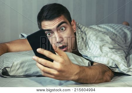 Young Frustrated And Stressed Man Is Late. He Is Waking Up, Looking At Smartphone And Is Shocked. Th