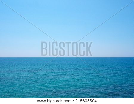 Blue ocean. A clear sunny day. Small waves. A direct horizon and an immense distance. Clear blue sky. There is not a single cloud.