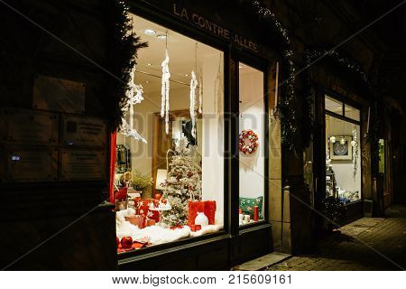 STRASBOURG FRANCE NOV 21 2017: Christmas decorations in store window showcase of a floral show pin Strasbourg France with multiple colorful globes vases and toys