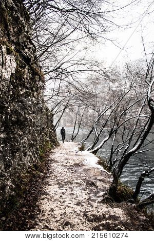 Lone man walk on mountain path by the water in cold snow weather as winter in plitvice lake background