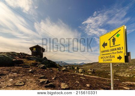 Mountain cabin for survival, close to Trolltunga in Norway. Sign pointing to survival cabin and to mountain guard.