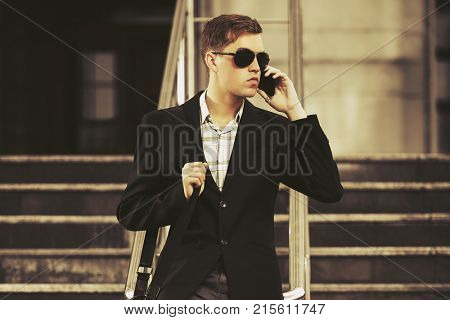 Young handsome business man calling on smartphone in city street. Stylish trendy male model in black blazer