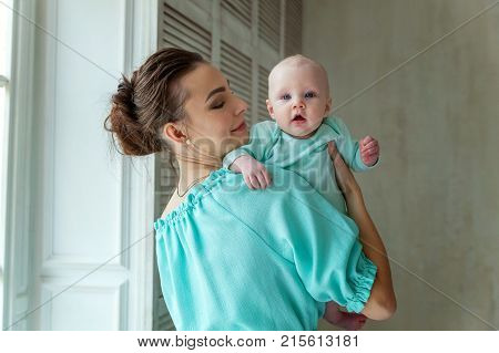 Mother holding her child. Young mother playing whith her daughter near the window. Woman and new born girl relax at home. Mother breast feeding baby. Happy family at home. Young mother playing whith her newborn daughter