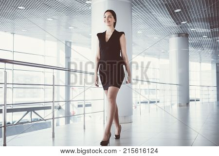 Closeup of smiling young beautiful business woman wearing dress and walking along office hallway. Low angle view.