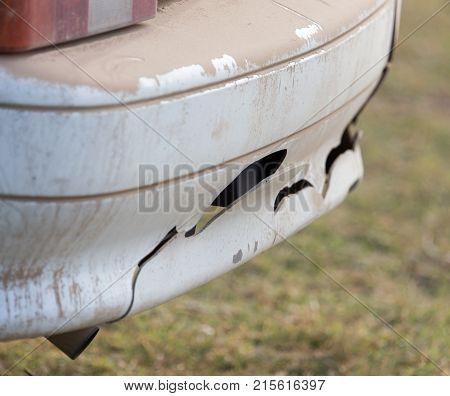 broken car bumper . In the park in nature