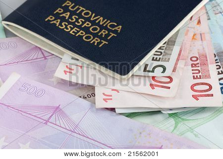 Several Euro banknotes in varions denominations with a passport on top of them. poster