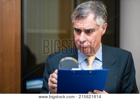 Businessman analyzing a document in his office