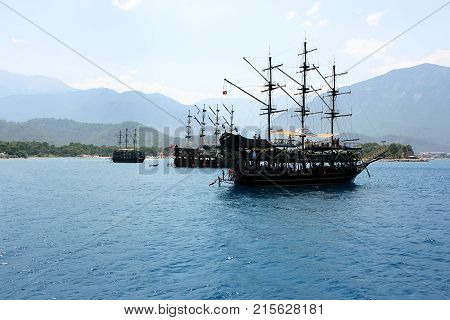 A pirate ship at the dock. Brick near the shore. The schooner in the turquoise sea. Sailing ship in the sea against the backdrop of the mountains. Tourist boat for walks. A ship with sails lowered.