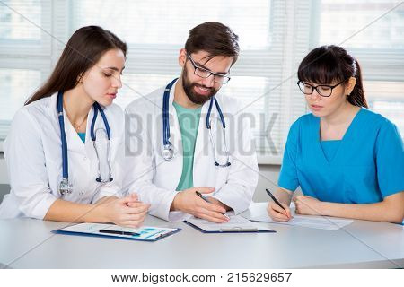 Group of doctors in the clinic discuss the diagnosis of the patient