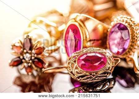 Elegant luxury composition of gold jewelry with ring with red amethyst and ruby gemstone and diamonds on light background close-up macro and reflection.