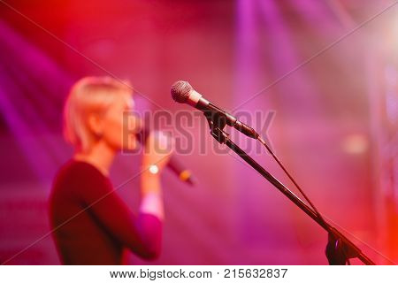 Microphone. Microphone for karaoke stands on stage. Close-up of light soffit, silhouette of speaker